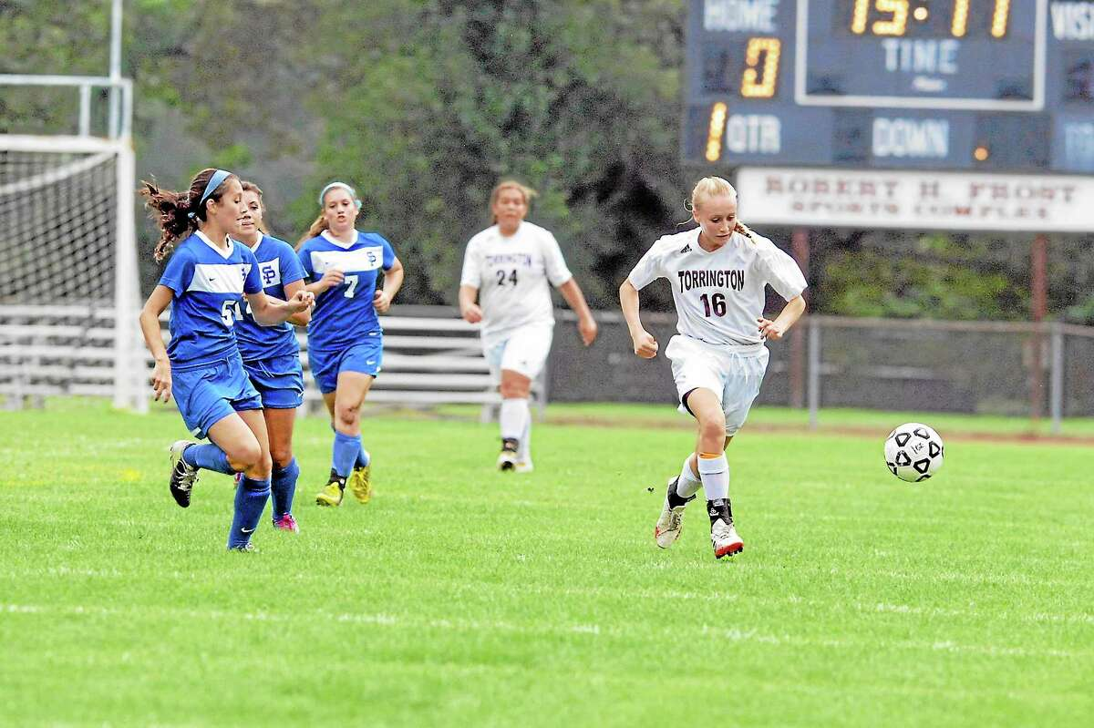 Torrington's Paige Middleton takes the ball up field as St. Paul defenders give chase.