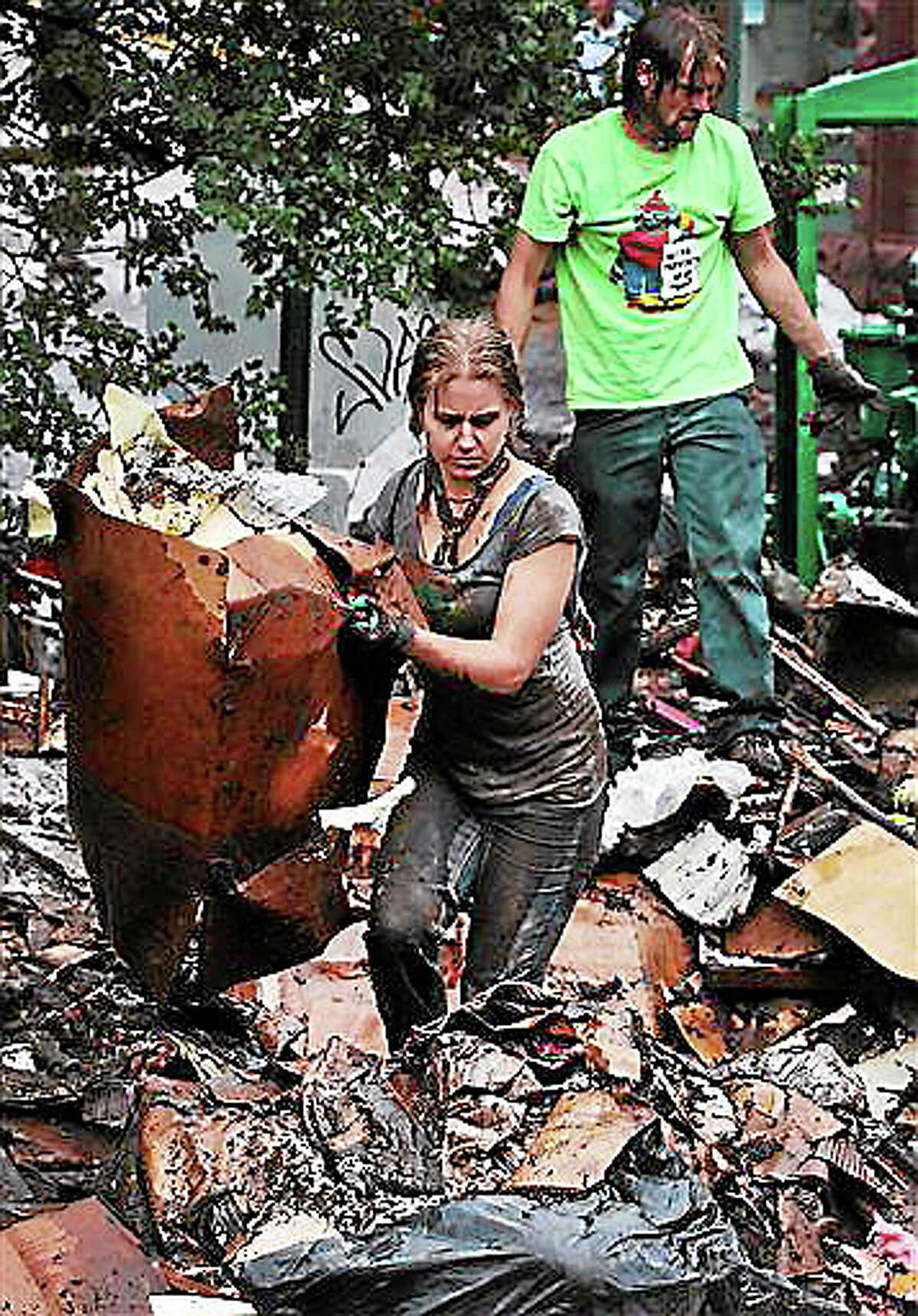In the rain, Erin Dettweiler, center, works with other local volunteers to clear away tons of mud-caked debris deposited in a recent flash flood, in Manitou Springs, Colo., Tuesday Aug. 13, 2013. Daily rainstorms have prompted new flash flood worries in Manitou Springs, which lies in the drainage of the area burned in last year's Waldo Canyon Fire. A 17-year-old girl drowned Monday after she was caught in heavy rain in Colorado Springs as storms pounded a region still reeling from mudslides and flash flooding that killed one person in nearby Manitou Springs last week. (AP Photo/Brennan Linsley)
