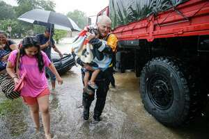 A rescuer carries a child from a boat to a pickup area along Edgebrook Sunday, August 27, 2017. Much of the area is flooded from rains after Hurricane Harvey.