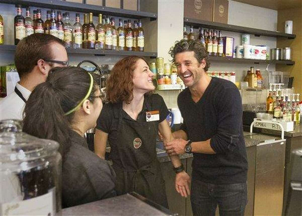 Patrick Dempsey's investment group has won the bid to purchase Tully's Coffee. Dempsey meets the staff at the Tully's Coffee on Western Avenue near the Pike Place Market on Friday, Jan. 4, 2013. Dempsey meets with employees from left including Stephen Loewen, Susie Campos and Sarah Paulson. (AP Photo/The Seattle Times, Mike Siegel)