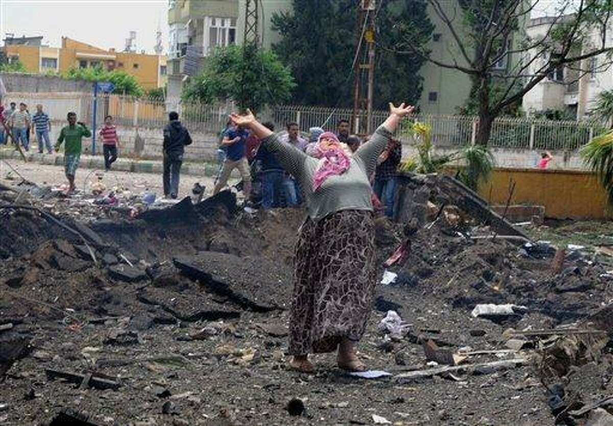 A woman cries at the scene of one of the explosion sites, after several explosions killed at least 18 people and injured dozens in Reyhanli, near Turkey's border with Syria, Saturday, May 11, 2013, Turkish Interior Minister Muammer Guler said.(AP Photo/Anadolu Agency, Cem Genco) TURKEY OUT