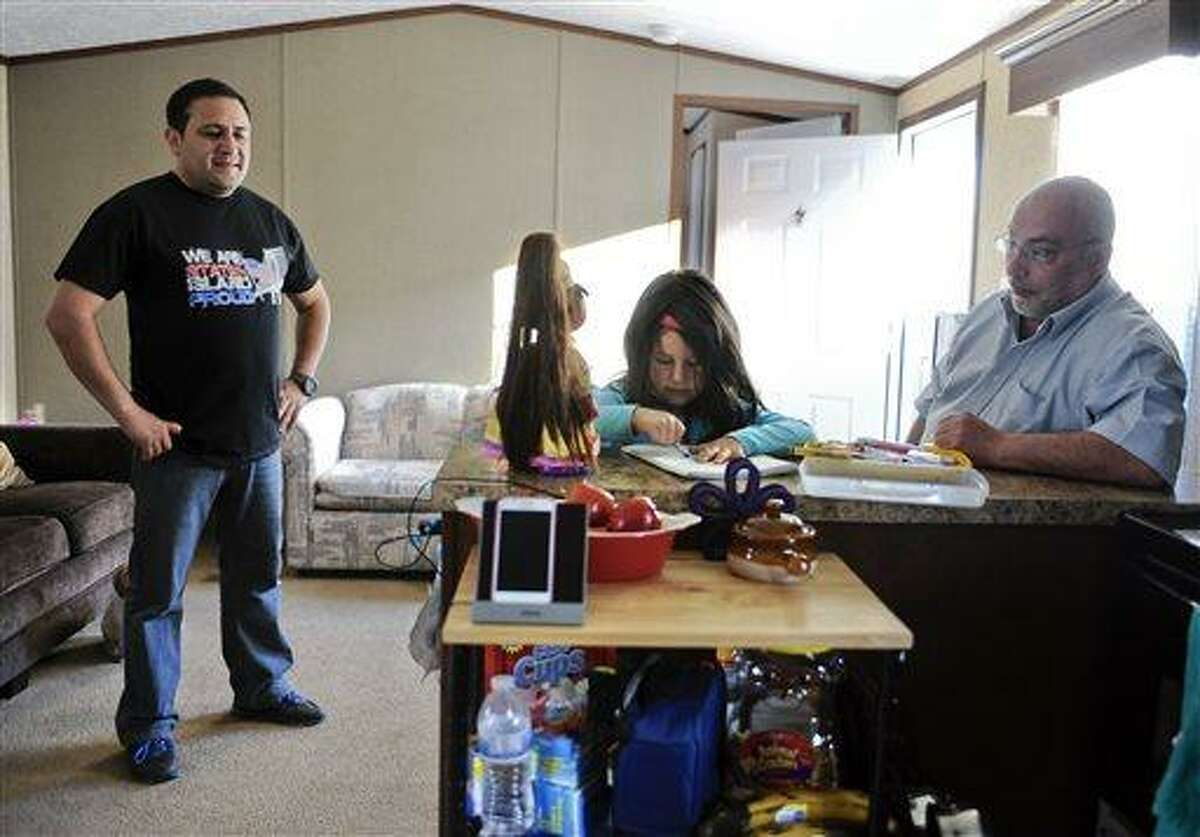 In this Sunday, May 5, 2013 photo, Guillermo Hernandez, left, and New Fairfield First Selectman John Hodge, right, watch Hernandez's daughter Vanessa draw inside the Hernandez family's mobile home in New Milford, Conn. Hernandez and his family are among 14 New York families displaced by Superstorm Sandy who were provided temporary housing at a makeshift mobile home park set up by former New Yorkers at Faith Church. (AP Photo/Jessica Hill)