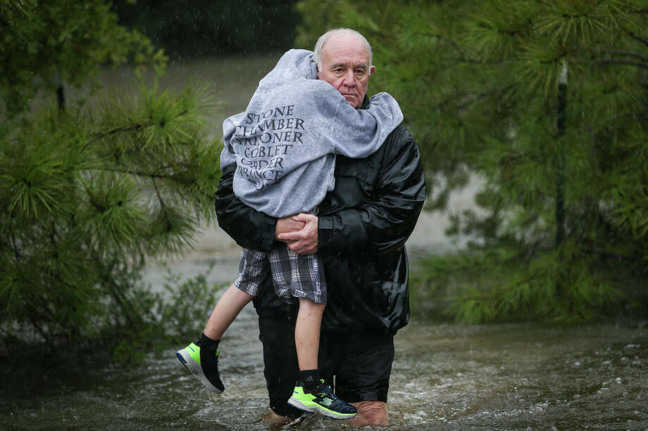 Charles Hawthorne carries his grandson Brittan, 9, as his daughter's family evacuates from the Timber Lakes/Timber Ridge subdivision on Sunday, Aug. 27, 2017, on Glen Loch Drive in Spring. Charles' daughter, Crystal, evacuated with her husband and three children from their home which was flooded with about two feet of water. (Michael Minasi / Chronicle) Photo: Michael Minasi, Staff Photographer / © 2017 Houston Chronicle