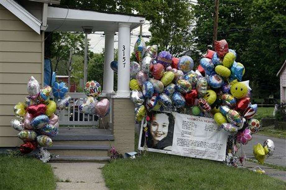 Balloons surround the porch at the home of Gina DeJesus in Cleveland Friday, May 10, 2013. DeJesus was freed Monday from the home of Ariel Castro where she and two other women had been held captive for nearly a decade.  (AP Photo/Mark Duncan) Photo: AP / AP