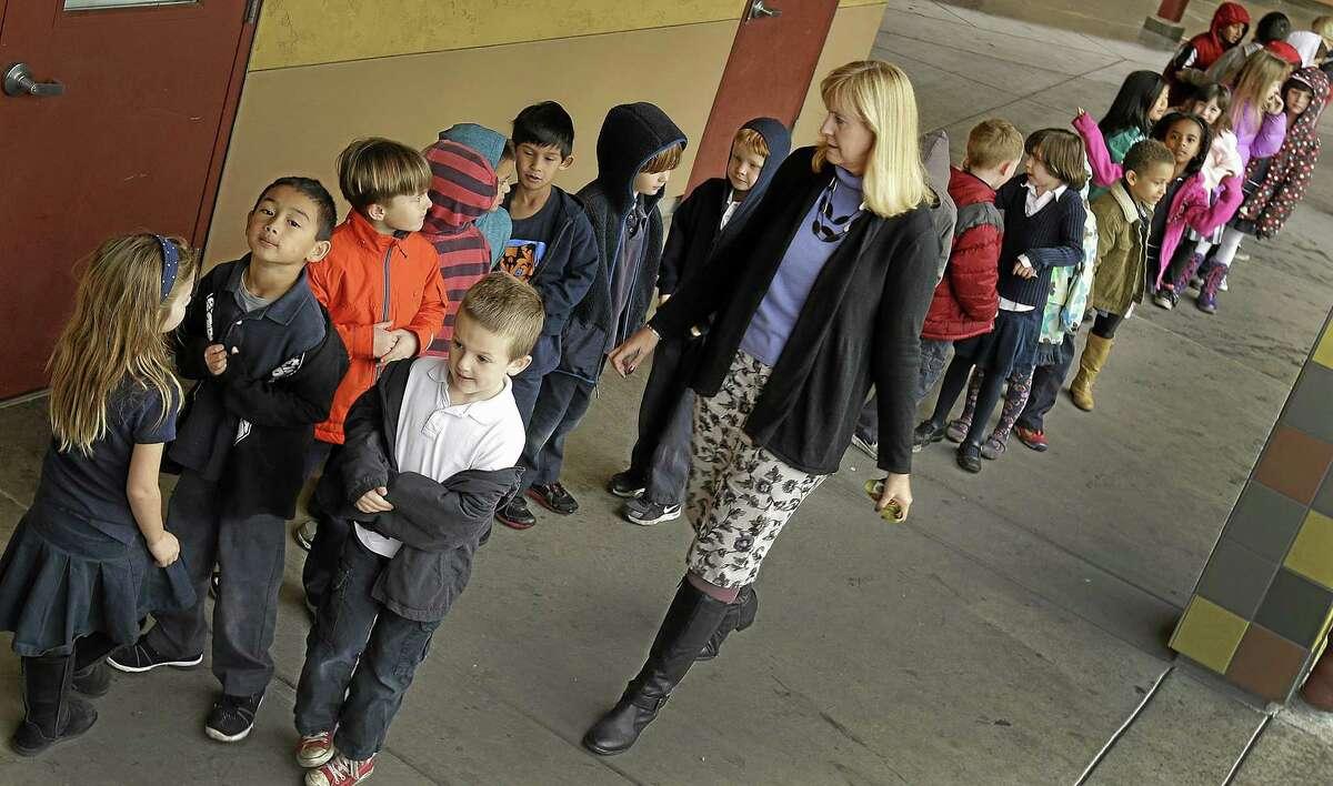 In this July 24, 2013 file photo, first grade teacher Lynda Jensen walks with her class of 30 children at Willow Glenn Elementary School in San Jose, Calif.