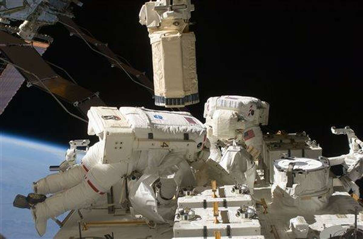 FILE - In this Monday July 27, 2009 image provided by NASA, astronauts Tom Marshburn, left, and Christopher Cassidy participate in a spacewalk for maintenance tasks. On Friday, May 10, 2013, the two astronauts are preparing for a possible impromptu spacewalk to work on a leaking ammonia coolant line. The line chills power systems but power was rerouted and is operating normally. The six-member crew is not in danger. NASA will decide Friday evening if the spacewalk is needed on Saturday. (AP Photo/NASA)