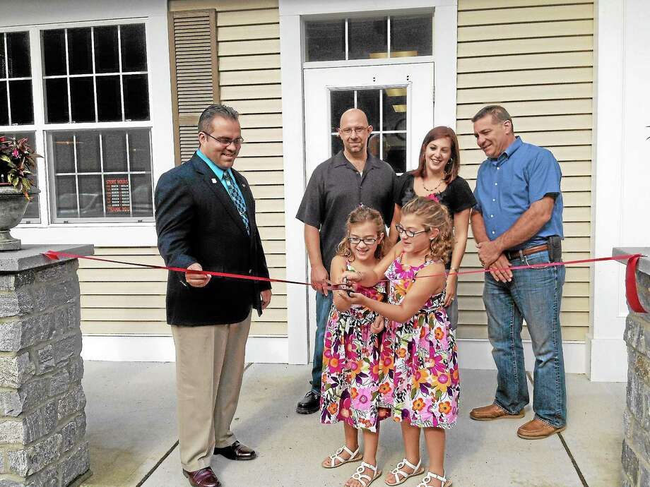 Six-year-old twins, Haley and Leah Czyz, cut the ribbon in front of the new Edison Grill and Eastside Electric, LLC. on Thursday. Kate Hartman - Register Citizen. Photo: Journal Register Co.