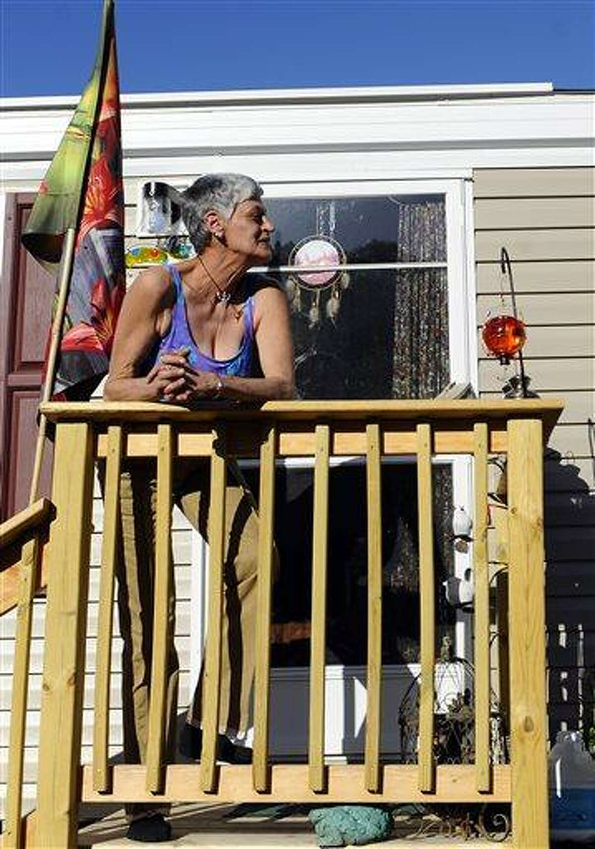 In this Sunday, May 5, 2013 photo, Maryann Daino stands outside her mobile home in New Milford, Conn. Daino is among the people displaced by Superstorm Sandy who were provided temporary housing at a makeshift mobile home park set up by former New Yorkers at Faith Church. (AP Photo/Jessica Hill)