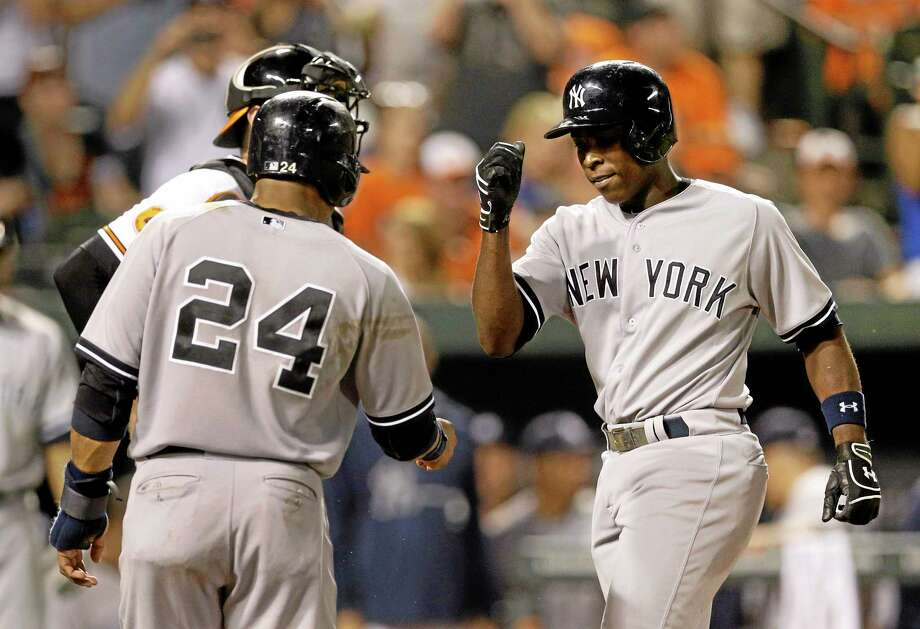 Patrick Semansky  — The Associated Press The Yankees' Alfonso Soriano, right, fist-bumps teammate Robinson Cano (24) after driving him in with a home run in the eighth inning of a game against the Baltimore Orioles on  Tuesday. New York won 7-5. Photo: AP / AP