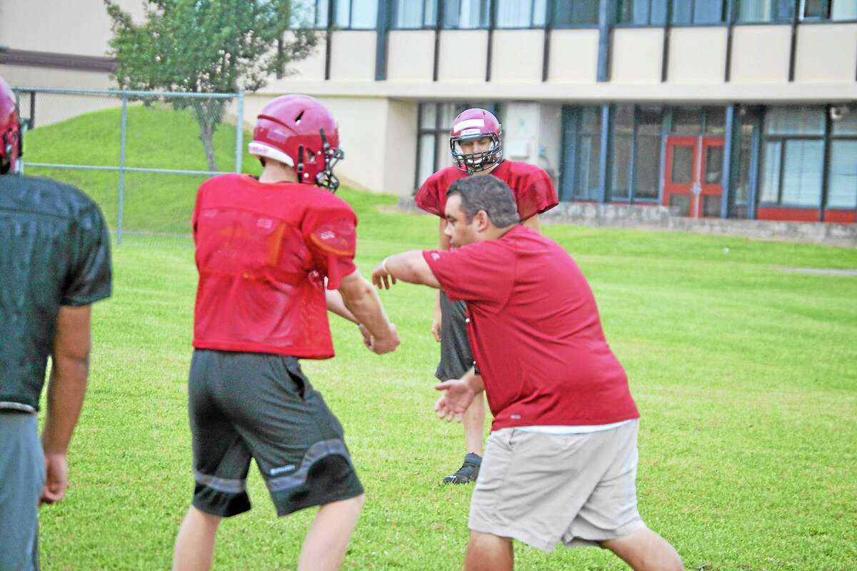 Gaitan Rodriguez shows his team a play during practice. Rodriguez played running back for Torrington High School from 1993-1996.