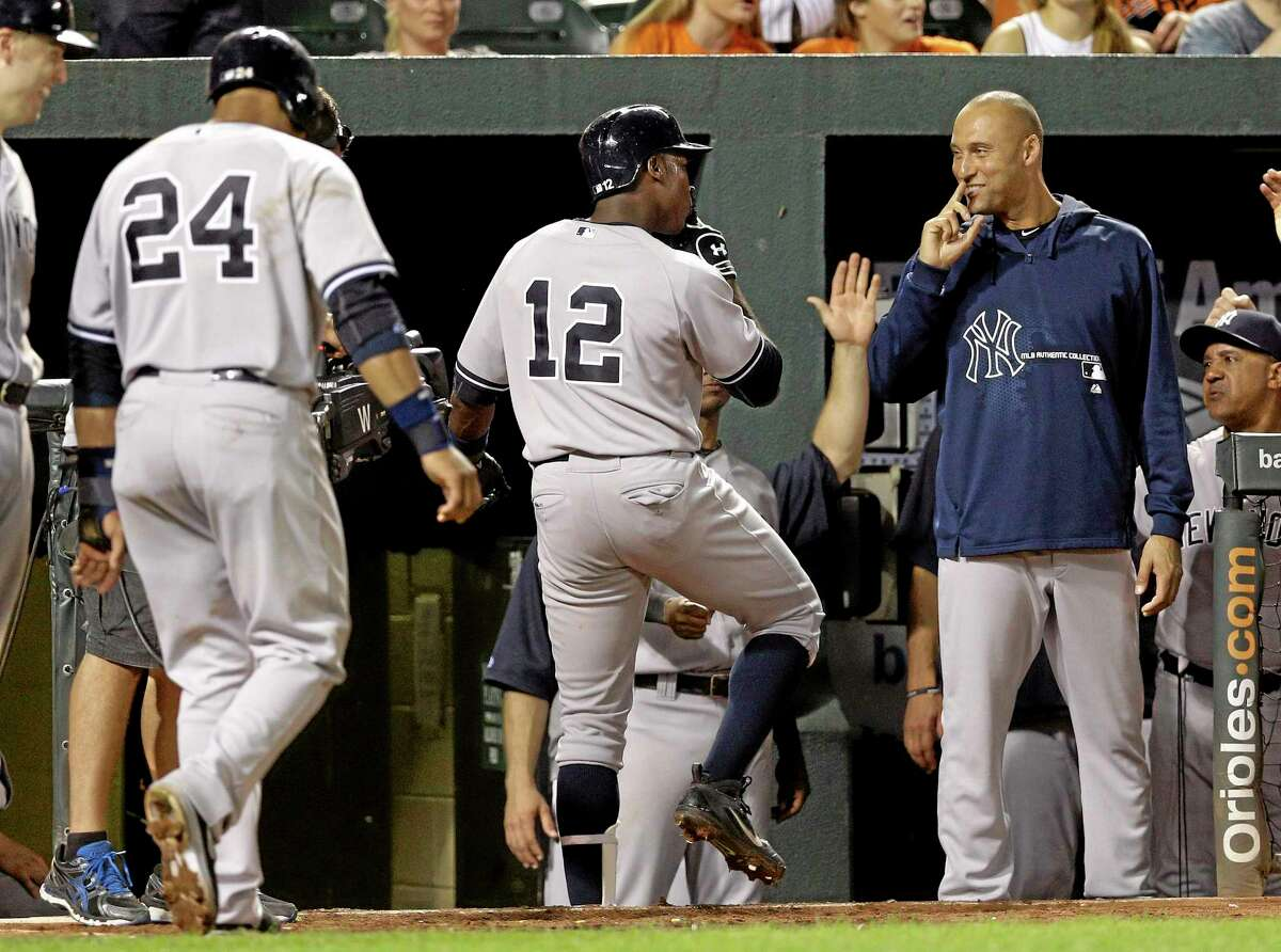 Derek Jeter welcomes Alfonso Soriano (12) and Robinson Cano (24) back to the dugout during Tuesday's game against the Orioles in Baltimore.