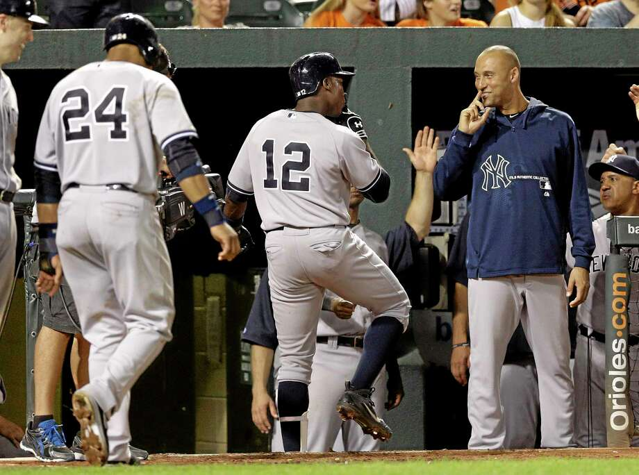 Derek Jeter welcomes Alfonso Soriano (12) and Robinson Cano (24) back to the dugout during Tuesday's game against the Orioles in Baltimore. Photo: PATRICK SEMANSKY — THE ASSOCIATED PRESS  / AP