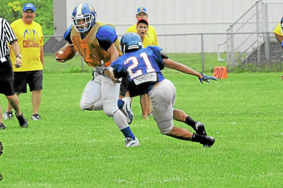 Gilbert-Northwestern running back Tony Ortiz attempts to run past a St. Paul defender during a preseason scrimmage. Photo: Laurie Gaboardi - Register Citizen