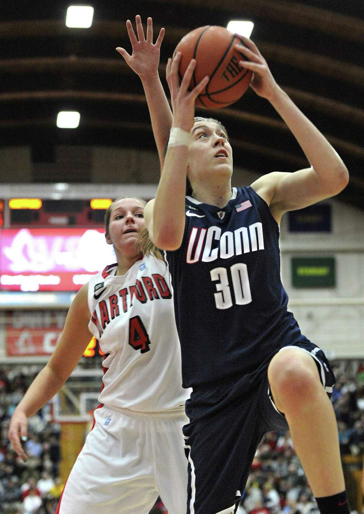 Connecticut's Breanna Stewart (30) goes up for a basket while guarded by Hartford's Christie Michals (4) during the second half of an NCAA women's college basketball game in West Hartford, Conn., Saturday, Dec. 22, 2012. Stewart was top scorer for Connecticut with 27 points in their 102-45 win over Hartford. (AP Photo/Jessica Hill)