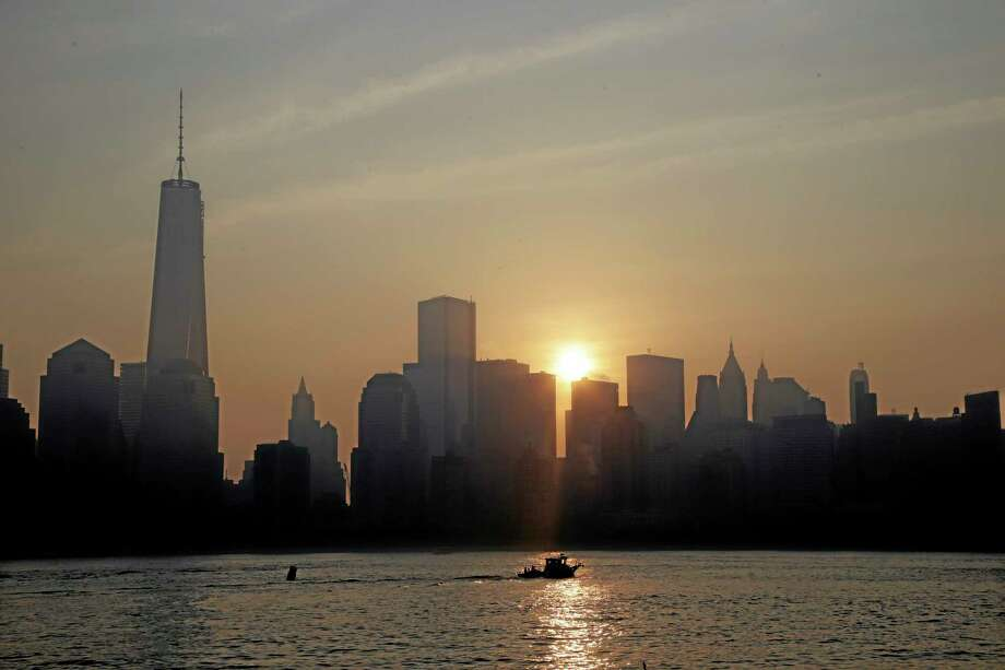The sun rises in back of One World Trade Center in lower Manhattan, seen from Jersey City, N.J., Wednesday, Sept. 11, 2013. Ceremonies will be held Wednesday to mark the 12th anniversary of the 9/11 terrorist attacks. (AP Photo/Mel Evans) Photo: AP / AP
