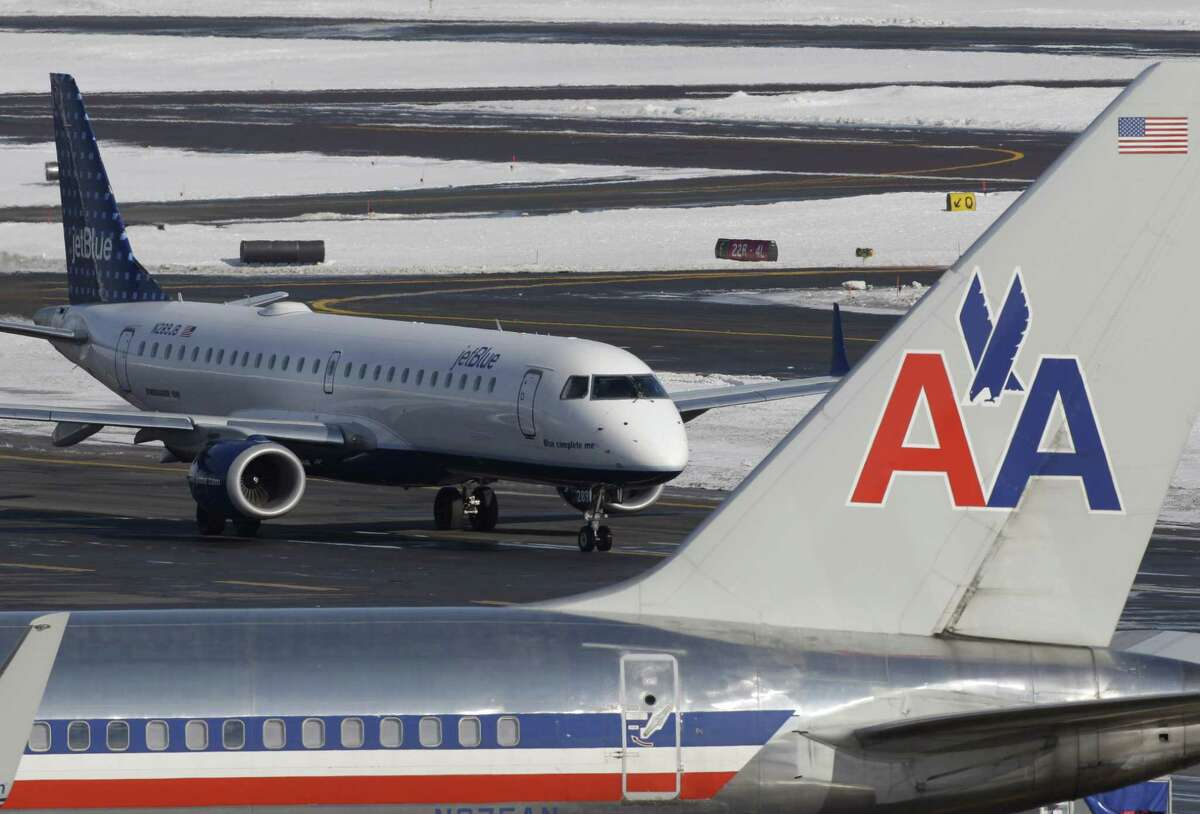 In this Thursday, Jan. 20, 2011 photo a Jet Blue jet taxis near an American Airlines jet parked at its gate at Boston's Logan International Airport. (AP Photo/Stephan Savoia) (Stephan Savoia)