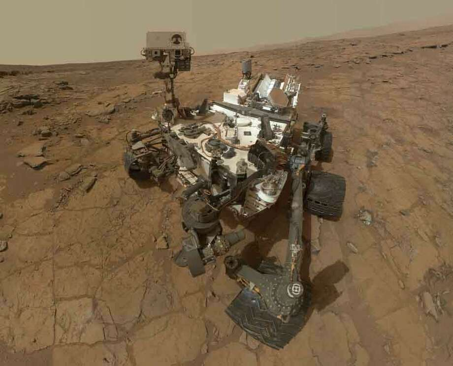 """On Sol 84 (Oct. 31, 2012), the Curiosity rover used the Mars Hand Lens Imager (MAHLI) to capture the set of thumbnail images stitched together to create this full-color self-portrait.This self-portrait documents the state of the rover and allows mission engineers to track changes over time, such as dust accumulation and wheel wear. Due to its location on the end of the robotic arm, only MAHLI is able to image some parts of the rover, including port-side wheels.The mosaic shows the rover at """"Rocknest,"""" the spot in Gale Crater where the mission's first scoop sampling took place. Scoop scars can be seen in the regolith in front of the rover. A portion of Mount Sharp appears on the right side. Mountains in the background to the left are the northern wall of Gale Crater.When the rover returns the full-resolution MAHLI frames of the scene, the team plans to generate a more detailed portrait of Curiosity in its Martian neighborhood."""