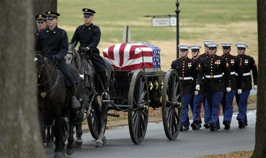 The casket of Marine Chief Warrant Officer 3 Gary L. Stouffer, of  Hubert, N. C., is brought on a caisson to the burial site at Arlington National Cemetery in Arlington, Va. Friday, Dec. 7, 2012. Stouffer, 37, was among four veterans killed when the float they were on was hit by a train during a parade in Midland, Texas on Nov. 15. (AP Photo/Susan Walsh) Photo: AP / AP
