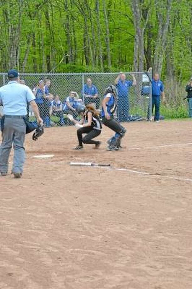 Pete Paguaga/Register Citizen  Thomaston's Shannon April slides into home and scoring from third base on an Alexa Torrence sacrifice fly.