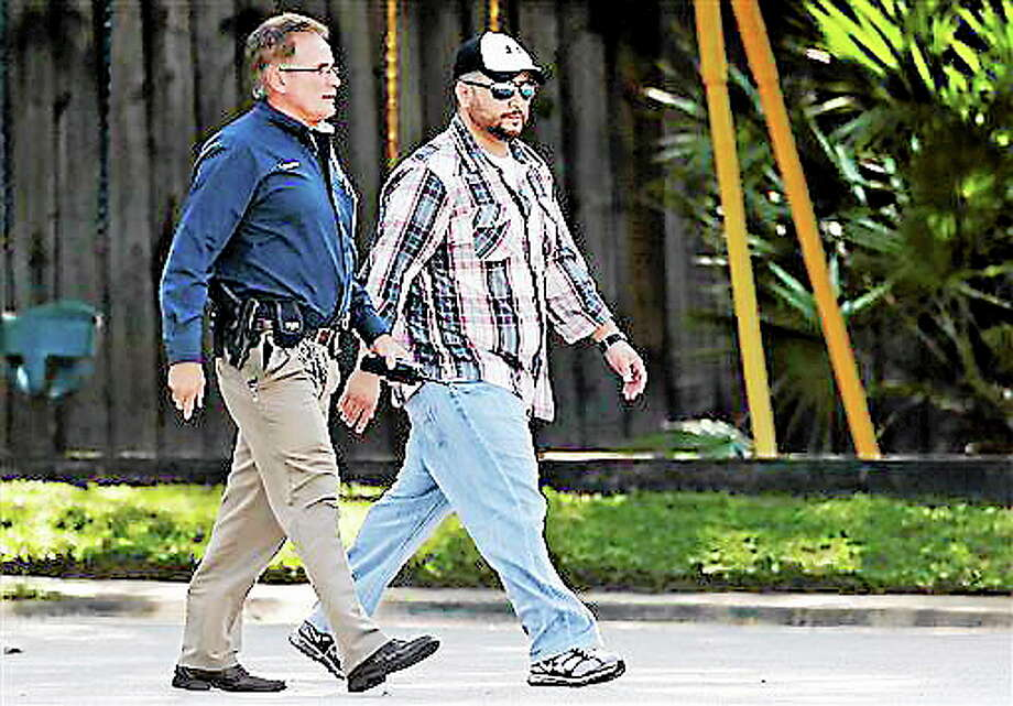 George Zimmerman, right, is escorted to a home by a Lake Mary police officer, Monday, Sept. 9, 2013, in Lake Mary, Fla., after a domestic incident in the neighborhood where Zimmerman and his wife Shellie had lived during his murder trial. Zimmerman's wife says on a 911 call that her estranged husband punched her father in the nose, grabbed an iPad out of her hand and smashed it and threatened them both with a gun. Zimmerman was recently found not guilty for the 2012 shooting death of Trayvon Martin. (AP Photo/John Raoux) Photo: AP / AP