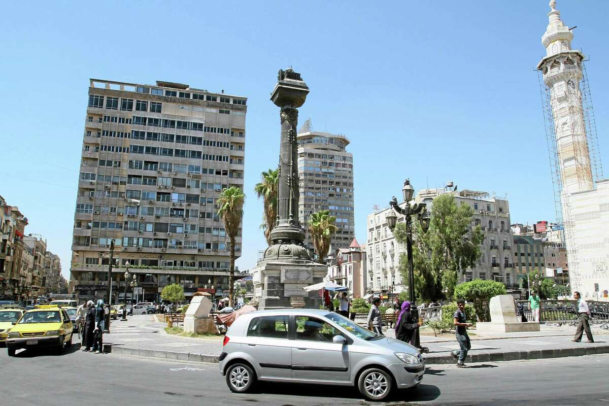 """A general view shows pedestrians and cars in al-Merjeh Square in Damascus, Syria, Tuesday, Sept. 10, 2013. An international human rights group said Tuesday that evidence """"strongly suggests"""" Syrian government forces fired rockets with warheads containing a nerve agent — most likely sarin — into a Damascus suburb in August, killing hundreds of people. (AP Photo)"""