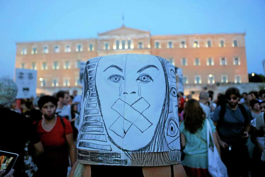 Art teachers protest against the government austerity measure that threaten their jobs, outside the Greek parliament in central Athens, on Friday, Sept, 6, 2013. The conservative-led government plans to sack 15,000 state employees by the end of 2014, and place another 25,000 in a program of mandatory suspensions and job transfers.  (AP Photo/Petros Giannakouris) Photo: AP / AP