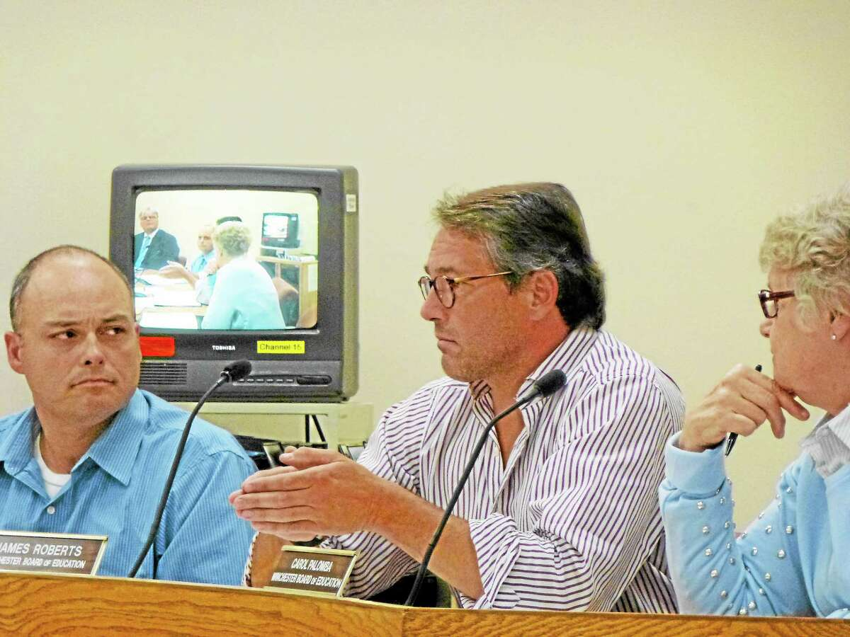 Board member James Roberts (center) debated possible ways for the district to counteract the town's insufficient funds.