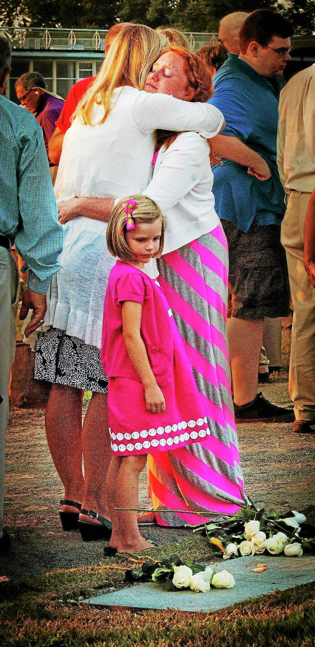 (Melanie Stengel — New Haven Register ) Emma Hunt, 13, of Essex hugs her Aunt Deborah Woodward, of Fairfieldw during the annual 9/11 memorial service in Westport. Hunt's father was killed in the attack on the World Trade Center. Looking at marker and flowere is Molly Woodward,5.