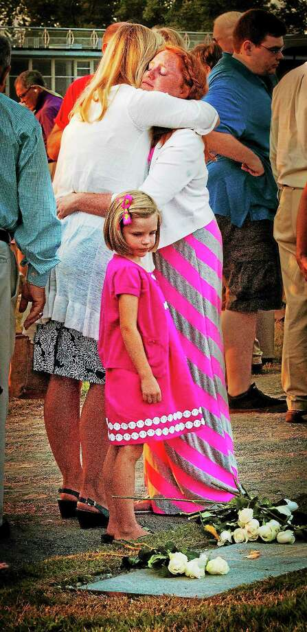 (Melanie Stengel — New Haven Register ) Emma Hunt, 13, of Essex hugs her Aunt  Deborah Woodward, of Fairfieldw during the annual 9/11 memorial service in Westport. Hunt's father was killed in the attack on the World Trade Center. Looking at marker and flowere is Molly Woodward,5. Photo: Journal Register Co.