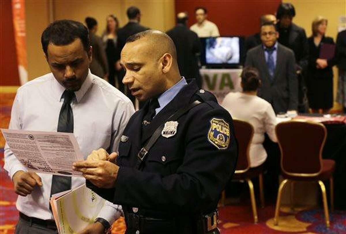 In this Tuesday, Feb. 26, 2013, photo, Philadelphia police recruiting officer Samuel Cruz, right, talks with Ismail Azeer of Carteret, N.J., at the Edison Career Fair job fair in the Iselin section of Woodbridge Township, N.J. The number of Americans seeking U.S. unemployment benefits fell sharply last week to a seasonally adjusted 346,000, suggesting March's weak month of hiring may be a temporary slowdown. Employers added only 88,000 jobs in March after averaging 220,000 the previous four months. The drop in unemployment benefits suggests hiring could pick up again in April. (AP Photo/Mel Evans)