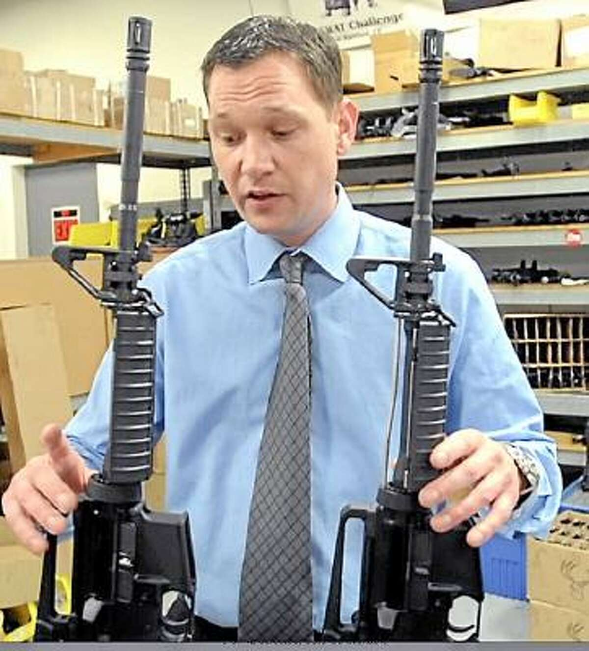 Mark Malkowski, President and CEO of Stag Arms in New Britain, displays the new Stag-22, left, a semi-automatic .22 rifle, an AR-15 looking product built from all AR-15 upper and lower components manufactured at his plant in New Britain but without a gas tube and at right is Stag Arms semi-automatic AR-15 banned in Connecticut. Thursday May 9, 2013. .Photo by Peter Hvizdak / New Haven Register