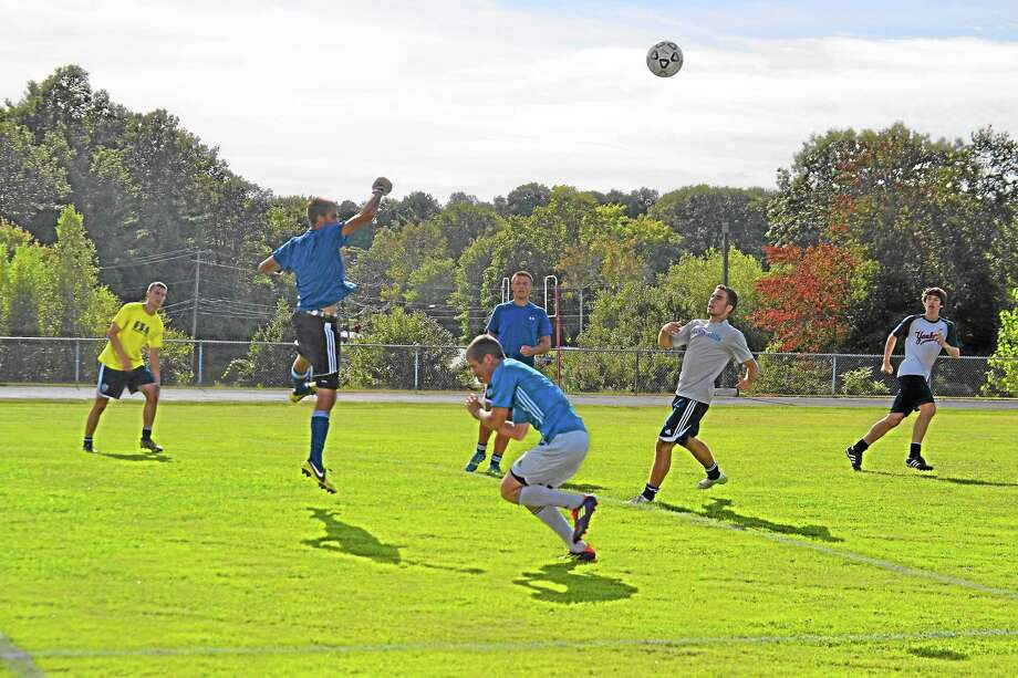 Alexander Daigle punches out a cross during Lewis Mills practice on Monday. Daigle will be the goalkeeper for the Spartans this season. Photo: Pete Paguaga—Register Citizen