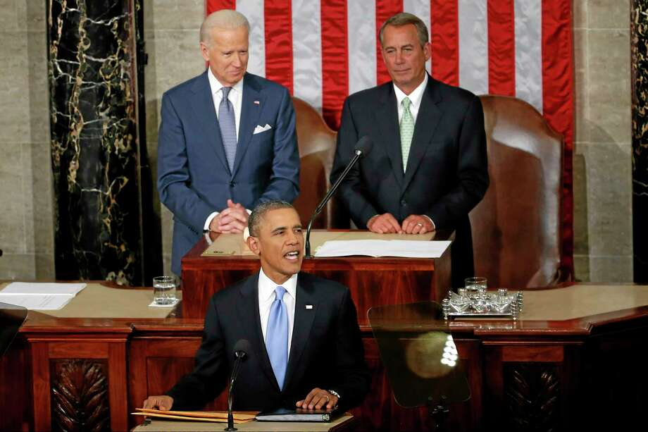 President Barack Obama takes the podium to give his State of the Union address on Capitol Hill in Washington, Tuesday Jan. 28, 2014. Vice President Joe Biden and House Speaker John Boehner of Ohio are behind the president. (AP Photo/Charles Dharapak) Photo: AP / AP