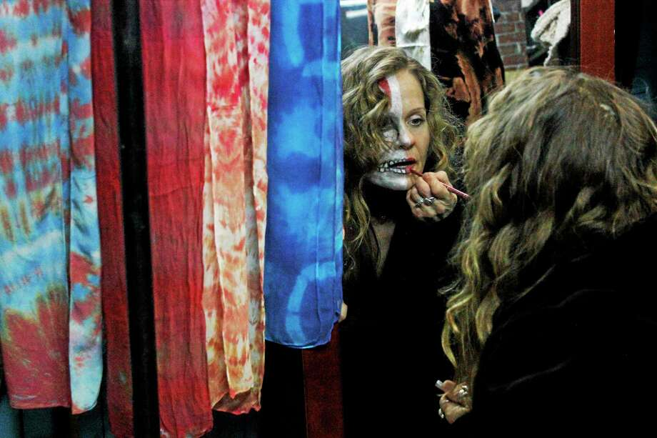 A woman touches up her makeup during a burlesque and variety show put on by The Desultory Theatre Club Saturday night at the old Morrisonís Hardware building on Water Street, which is now an art space run by CreateHereNow. Photo: Shako Liu—Register Citizen