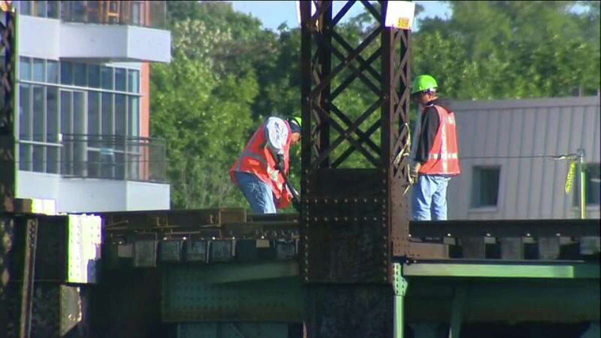 Workers fix a bridge over the Norwalk River that became stuck Thursday morning, causing major delays on Metro-North's New Haven Line during the busy weekday commute.