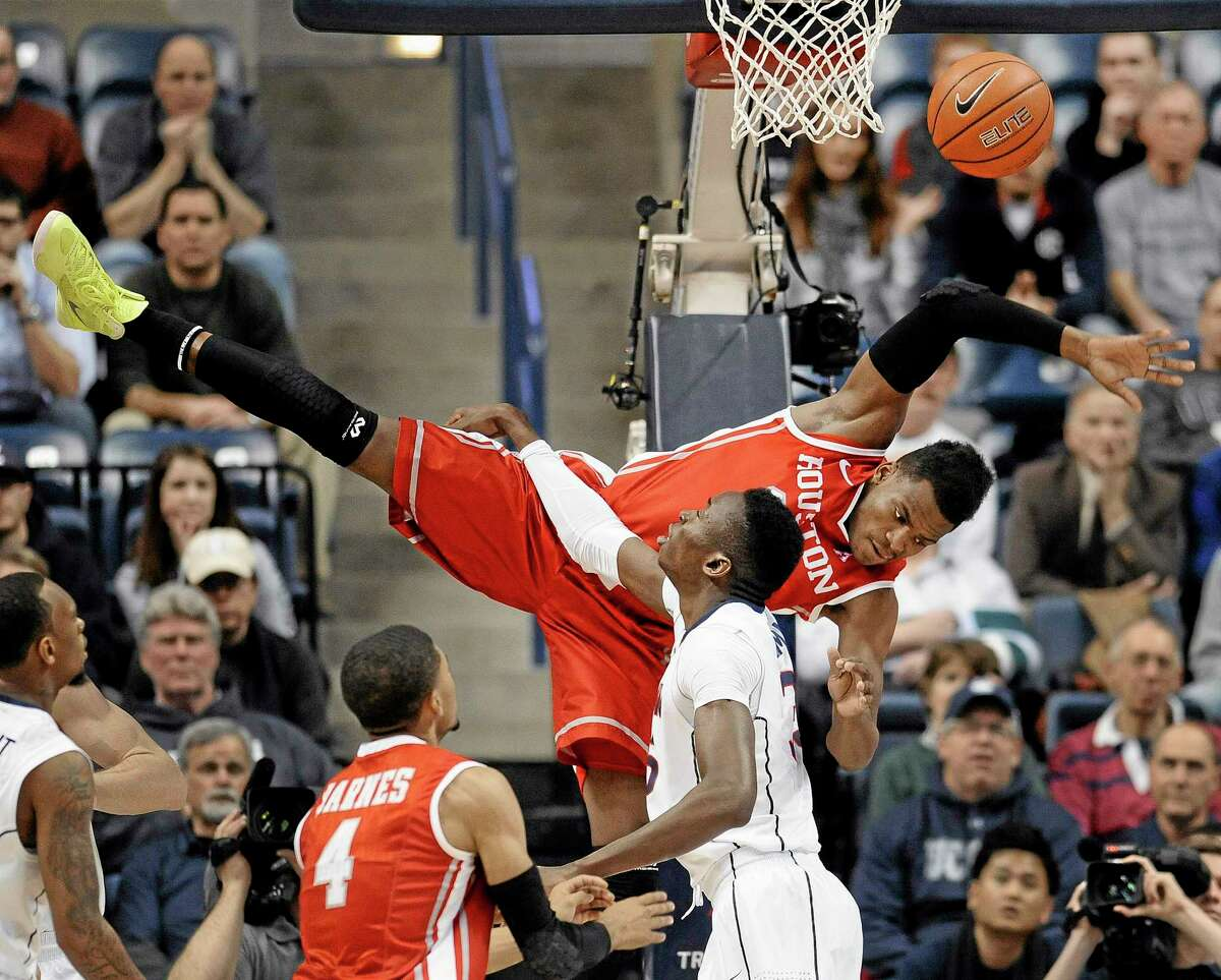 Houston's Danuel House falls to the court after missing a dunk as UConn's Amida Brimah, bottom right, defends during the first half of Thursday's game in Storrs.