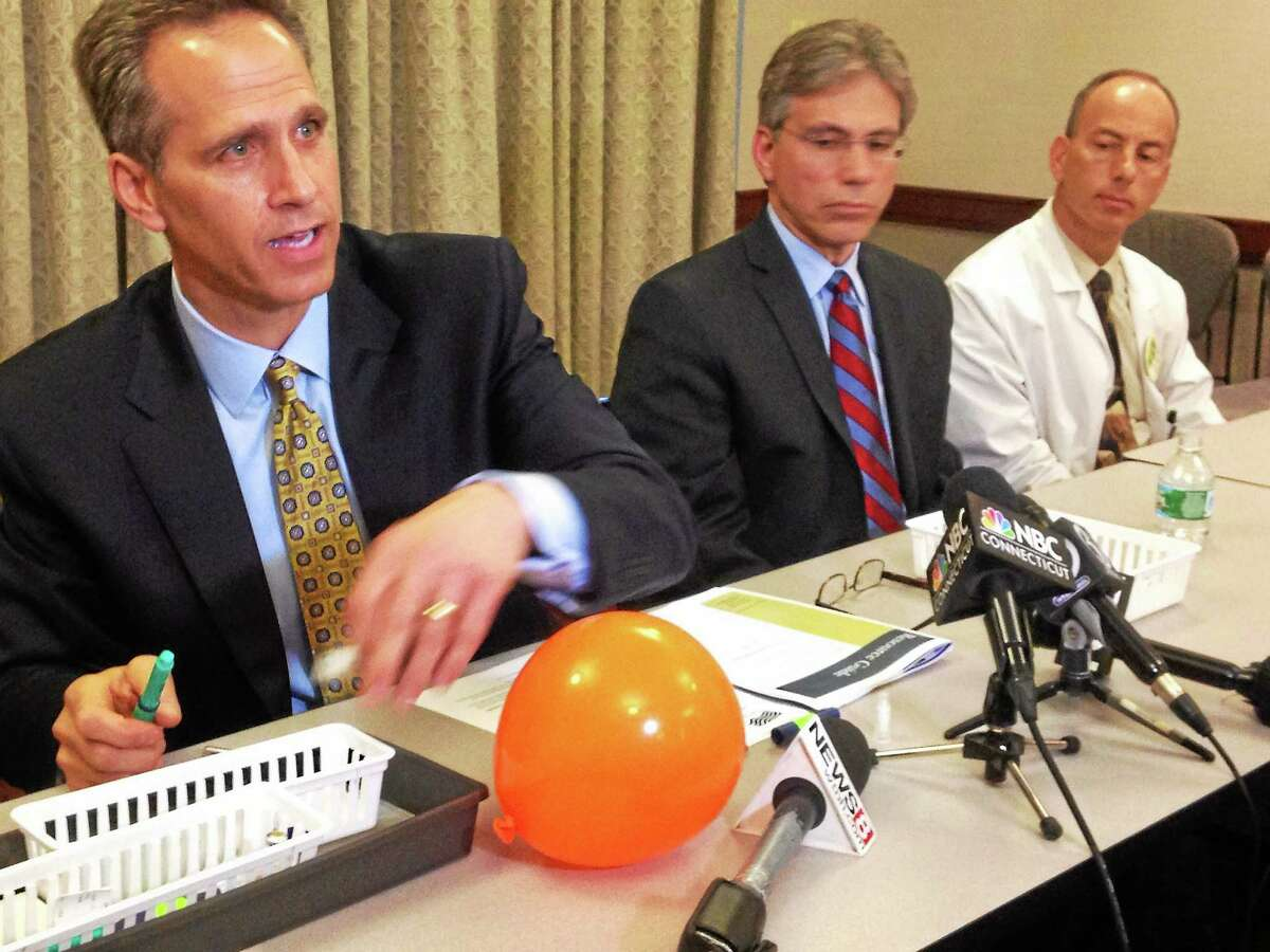 Griffin Hospital President and CEO Patrick Charmel, left, demonstrates how the insulin pen was misused used. Dr. Harold Schwartz, center, the chief of gastroenterology and D. Howard Quentzel, chief of infectious diseases.