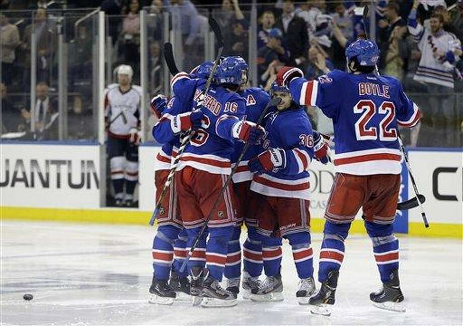 New York Rangers celebrate after Dan Girardi scored in the third period of Game 4 of their first-round NHL Stanley Cup playoff series in New York, Wednesday, May 8, 2013. The Rangers evened the series by defeating the Capitals 4-3.  (AP Photo/Kathy Willens) Photo: AP / AP