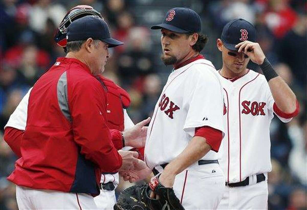 Boston Red Sox manager John Farrell, left, takes the ball from Joel Hanrahan, center, after Hanrahan put two men on base in the ninth inning of a baseball game against the Tampa Bay Rays in Boston, Saturday, April 13, 2013. (AP Photo/Michael Dwyer)