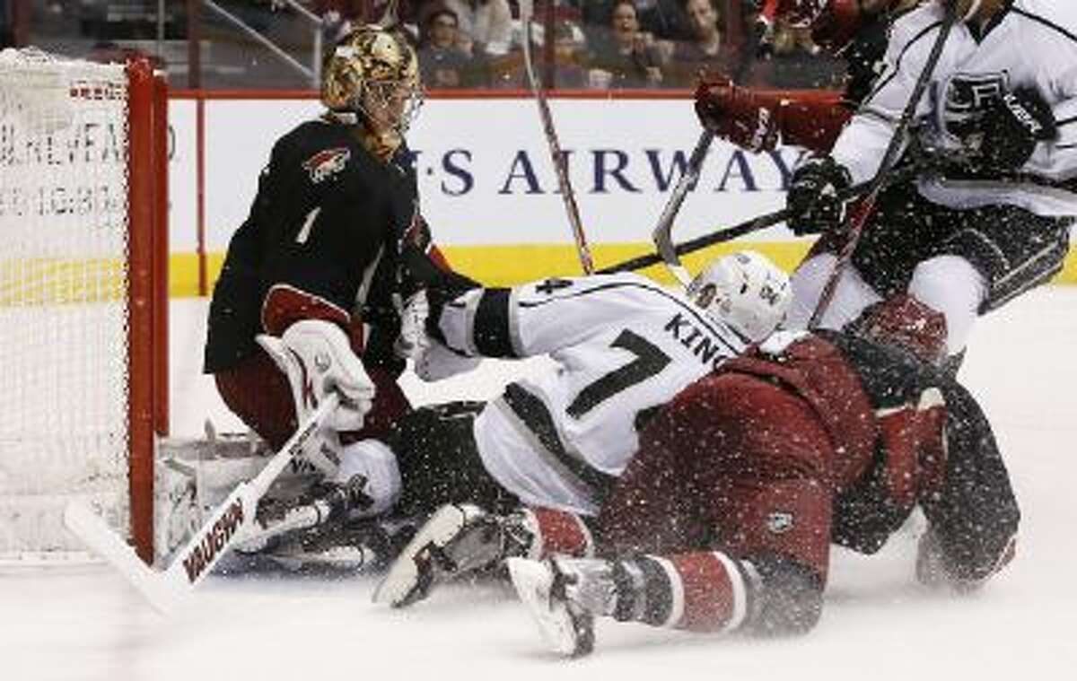Phoenix Coyotes' Zbynek Michalek, right, of the Czech Republic, and Los Angeles Kings' Dwight King, middle, slide into Coyotes goalie Thomas Greiss (1), of Germany, during the first period of an NHL hockey game Tuesday, Jan. 28, 2014, in Glendale, Ariz.