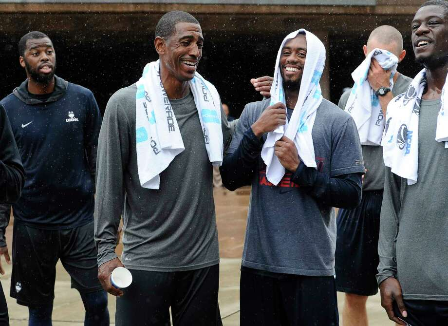 Connecticut NCAA college basketball head coach Kevin Ollie, second from left, shares a light moment with player Ryan Boatright, right, after the Husky Run, Wednesday, Oct. 1, 2014, in Storrs, Conn. (AP Photo/Jessica Hill) Photo: AP / FR125654 AP