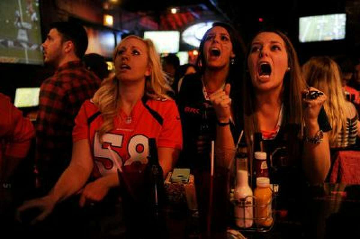 Becky Roth, 22, right, lets out a frustrated yell during the closing minutes of the second quarter as Megan Noe, 24, left, and Maggie Roth, 24, look on during a Super Bowl XLVIII watch party at Jackson's Bar in Denver Sunday.