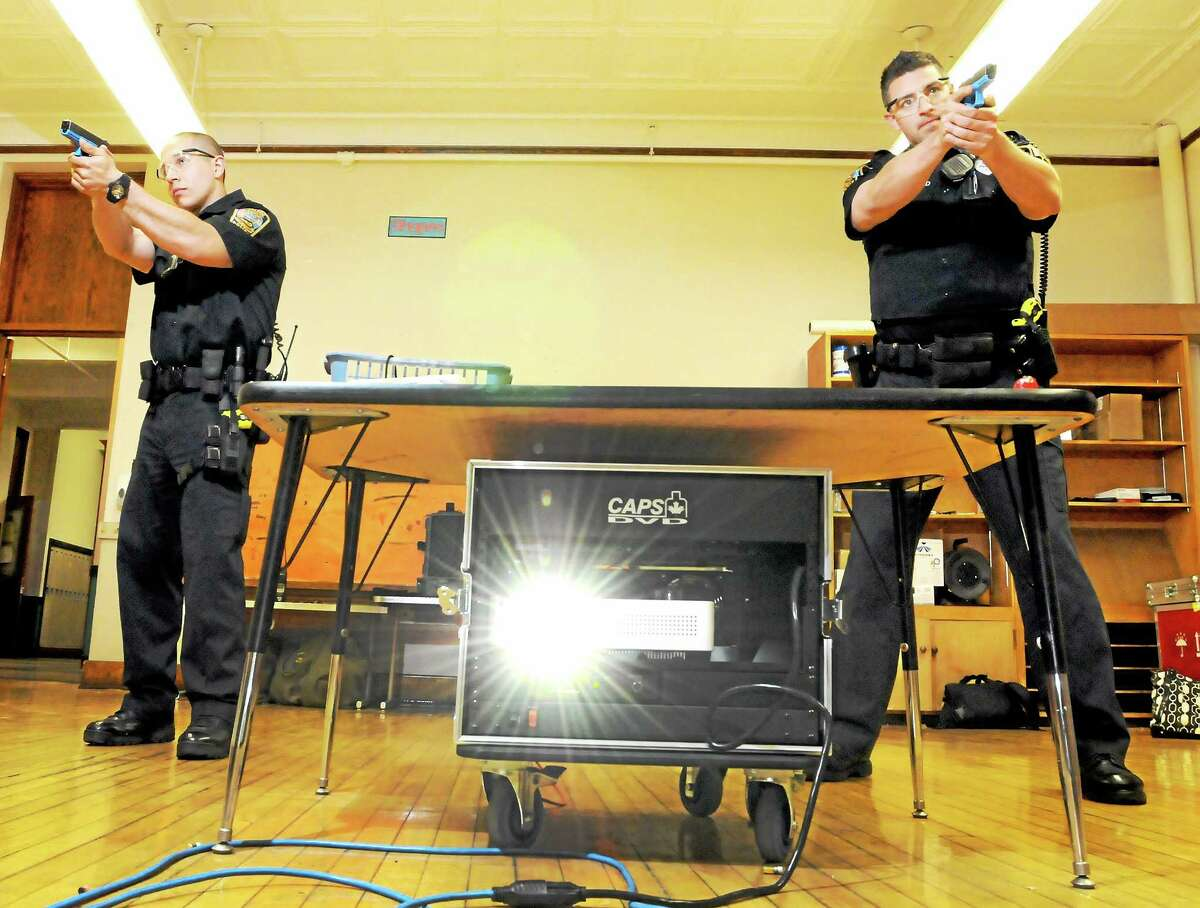 Bristol police officers Jason Kasparian, center, and Eric Wethered, right, during a shooting training session Wednesday, May, 8, 2014 in a vacant school building in Bristol using the CAPS firearms judgement training system.