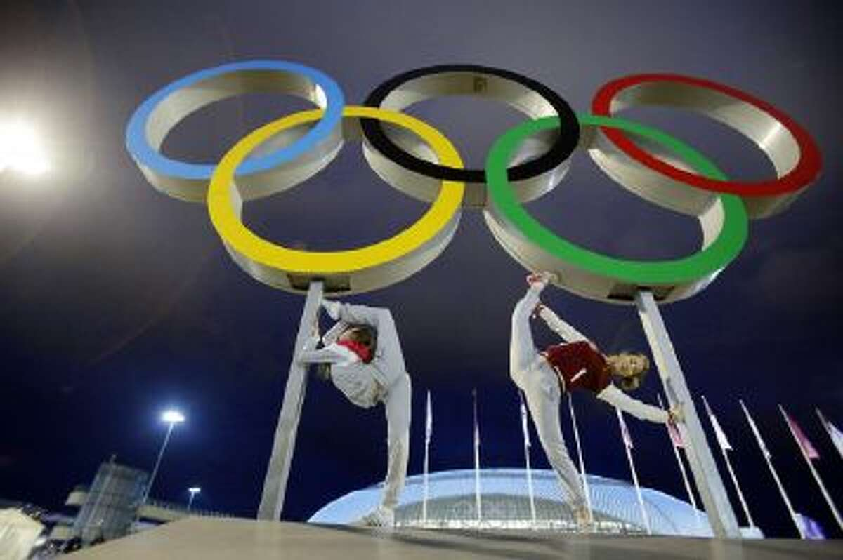Russian dancers who will be performing at the Opening Ceremony pose with the Olympic rings as their friend photographs them, ahead of the 2014 Winter Olympics Thursday in Sochi, Russia.