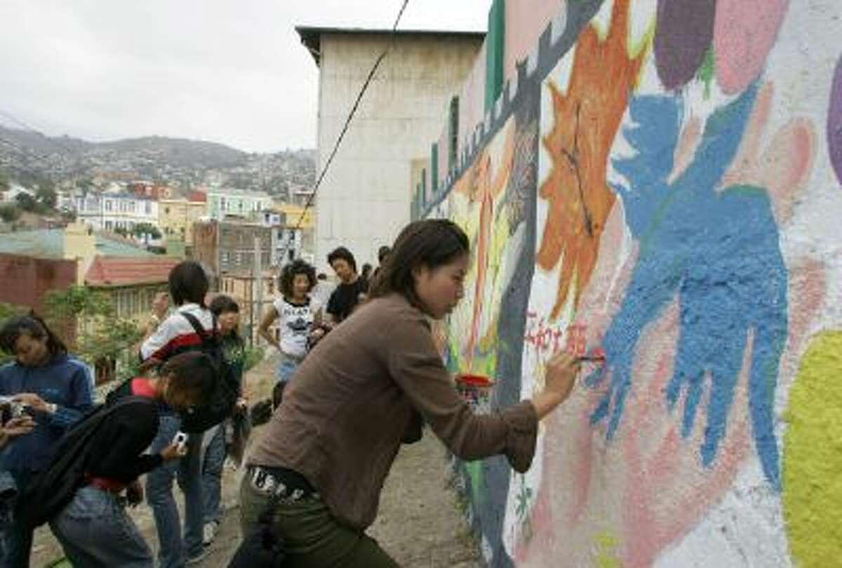 Japan's Tomomi Kondo paints a pro-peace mural in Valparaiso, Chile.