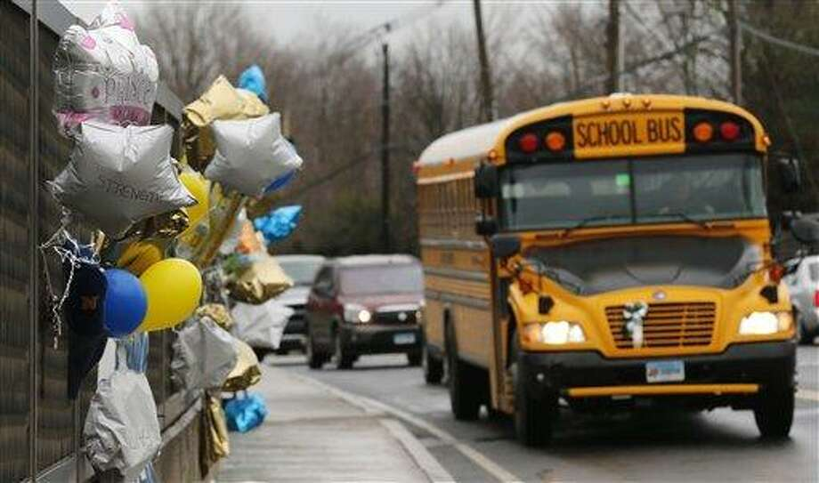 FILE - In this Dec. 18, 2012 file photo, a school bus rolls toward a memorial in Newtown, Conn., for victims of the Sandy Hook Elementary School shooting. Nearly three weeks after the shooting rampage, classes are starting Thursday, Jan. 3, 2013 for the Sandy Hook students at a repurposed school in the neighboring town of Monroe, where the students' desks have been taken along with backpacks and other belongings that were left behind in the chaos following the shooting on Dec. 14. (AP Photo/Charles Krupa, File) Photo: AP / AP