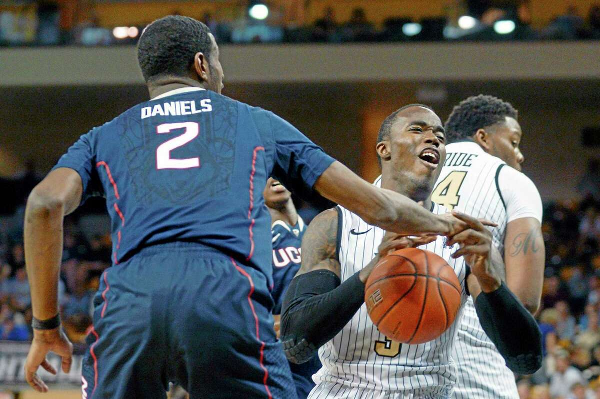 Central Florida guard Isaiah Sykes, right, is fouled by Connecticut forward DeAndre Daniels (2), while driving to the basket, during the second half of an NCAA college basketball game in Orlando, Fla., Sunday, Feb. 9, 2014. Connecticut won 75-55. (AP Photo/Phelan M. Ebenhack)