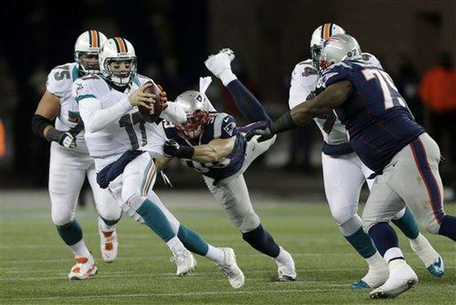 New England Patriots defensive end Trevor Scott (99) tries to tackle Ryan Tannehill during the third quarter of an NFL football game in Foxborough, Mass., Sunday, Dec. 30, 2012. (AP Photo/Charles Krupa) Photo: ASSOCIATED PRESS / AP2012