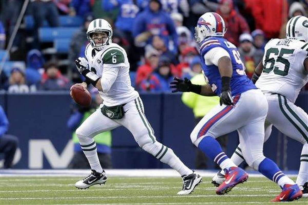 New York Jets quarterback Mark Sanchez (6) scrambles away from Buffalo Bills defensive end Alex Carrington (92) during the second half of an NFL football game on Sunday, Dec. 30, 2012, in Orchard Park, N.Y. (AP Photo/Gary Wiepert)
