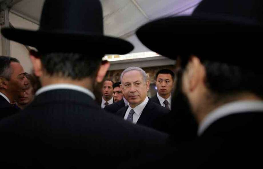 Israeli Prime Minister Benjamin Netanyahu, center, meets rabbis as he visits the Shanghai Jewish Refugees Museum at former site of Ohel Moshe Synagogue in Shanghai, China, Tuesday, May 7, 2013. China is hosting both the Palestinian and Israeli leaders this week in a sign of its desire for a larger role in the Middle East. (AP Photo/Eugene Hoshiko) Photo: AP / AP